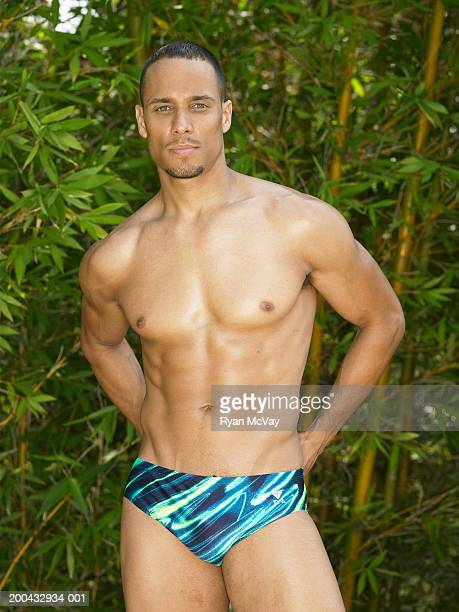 man in racing briefs standing with hands behind back, portrait - black men in speedos stock photos and pictures