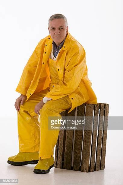 Man in rain gear sitting on wooden crate