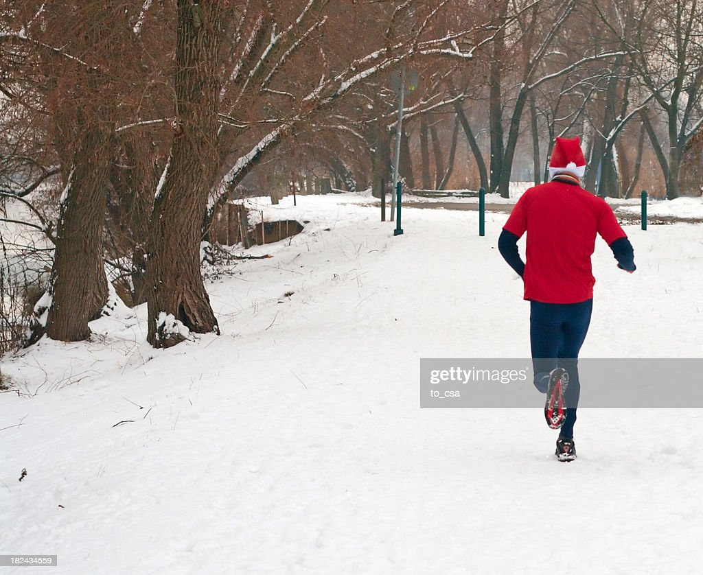 Man in red running in the snow : Stock Photo