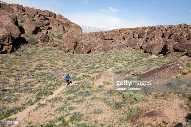 Man in red shirt trail running.