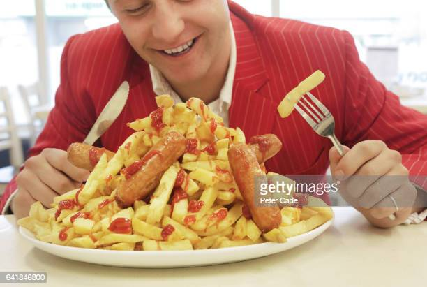 Man in red suit eating large plate of sausages and chips