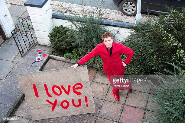 man in red suit holding 'i love you' sign - love you stock photos and pictures