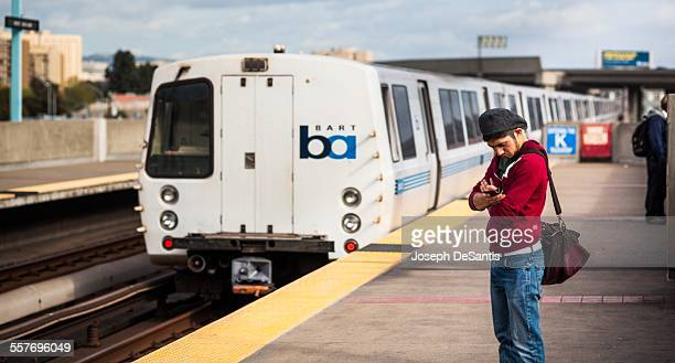 Man in red sweater hat and sling bag with arms folded looks at his smartphone A BART train is in the background Oakland California Taken March 24 2015