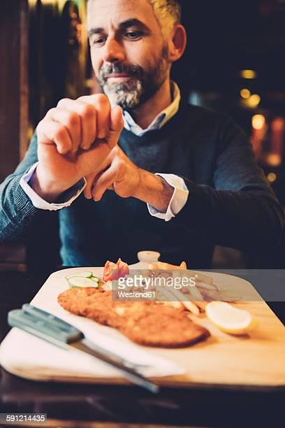 Man in restaurant having Wiener Schnitzel with French fries