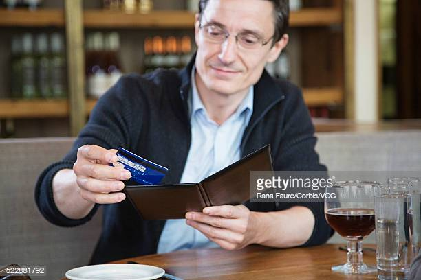 Man in restaurant paying with credit card