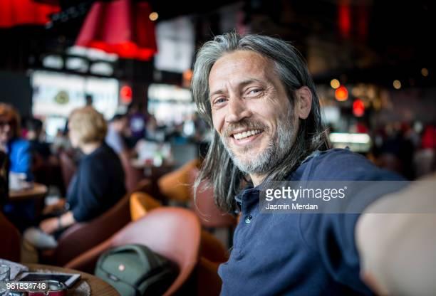 man in restaurant taking self portrait - selfie stock-fotos und bilder