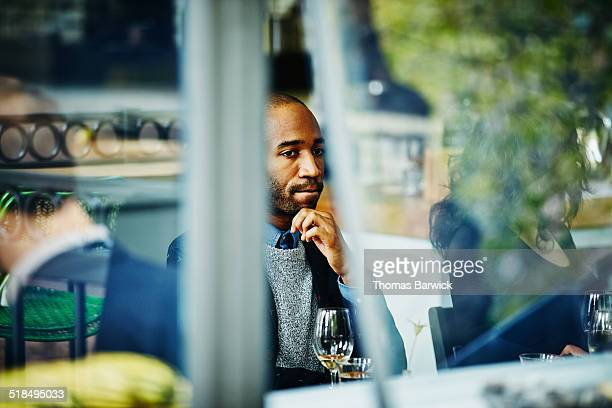 Man in restaurant with friends view through window
