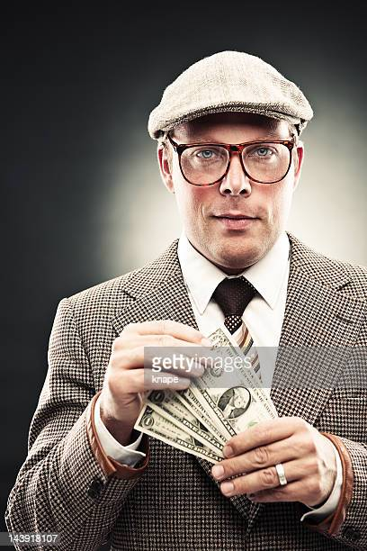 man in retro suit counting money - brown suit stock photos and pictures