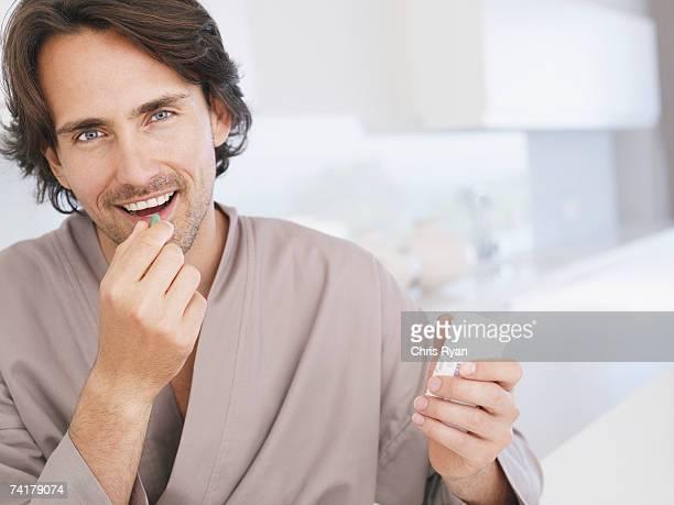 Mann in Bademantel hält Vitamintablette