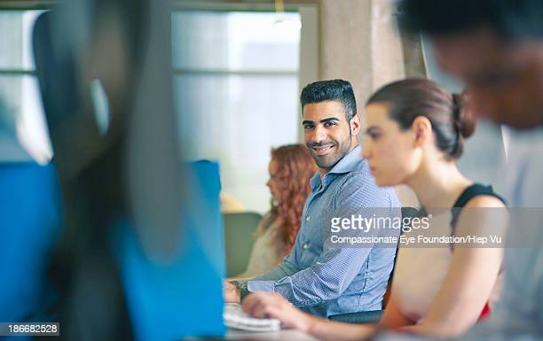 Man in row of office workers, smiling