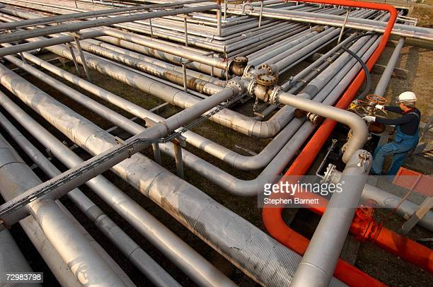 man in safety clothing closing valve on oil refinery elevated view - closing stock photos and pictures