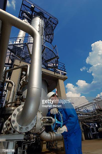 man in safety clothing closing valve on oil refinery - air valve stock photos and pictures