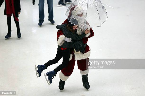 A man in Santa Claus attire skates with a young girl while holding an umbrella at the skating rink at Rockefeller Center on December 22 2015 in New...