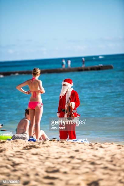 man in santa claus costume talking to tourists on the beach, hawaii, usa - honolulu foto e immagini stock