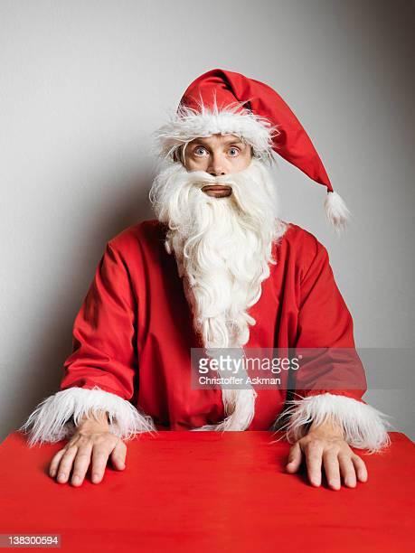 man in santa claus suit sitting at table - bad santa stock pictures, royalty-free photos & images