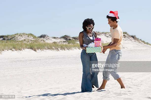 Man in Santa hat giving woman gifts on beach