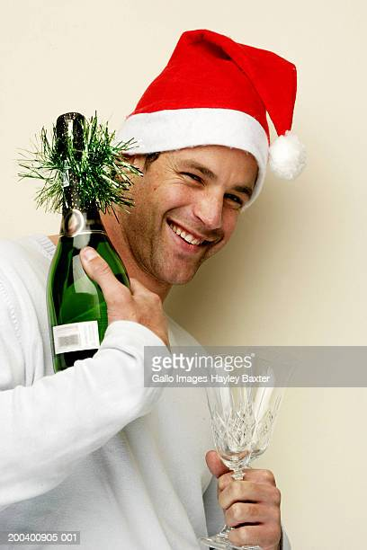 Man in Santa hat holding bottle of champagne and glasses, portrait