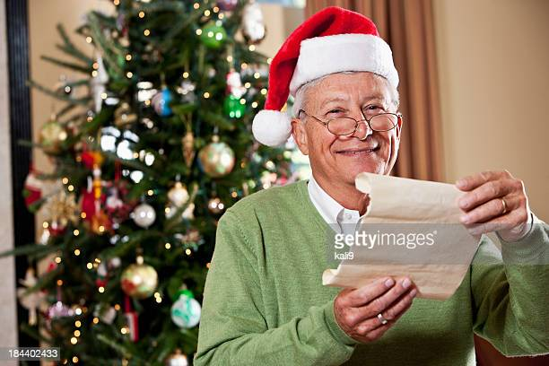 man in santa hat reading christmas wishlist - green hat stock pictures, royalty-free photos & images
