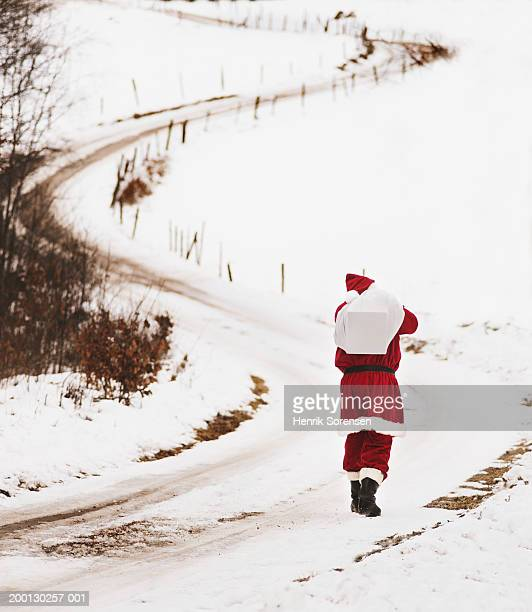 man in santa suit with sack over shoulder on snowy lane, rear view - 布の袋 ストックフォトと画像