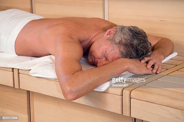 Mature man relaxing in sauna, eyes closed