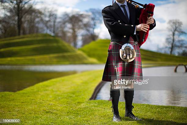 Man in Scottish kilt playing bagpipes