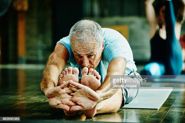 man in seated forward bend pose during yoga class - sportlichkeit stock-fotos und bilder
