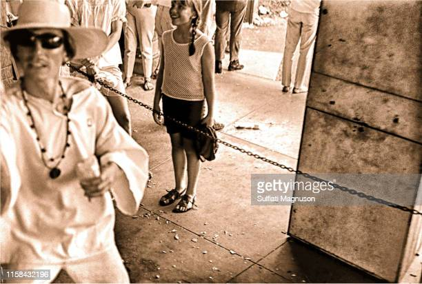 Man in shades, all dressed in white with 2 necklaces and a straw hat making offerings to riders of the carousel, a young girl transfixed by the...