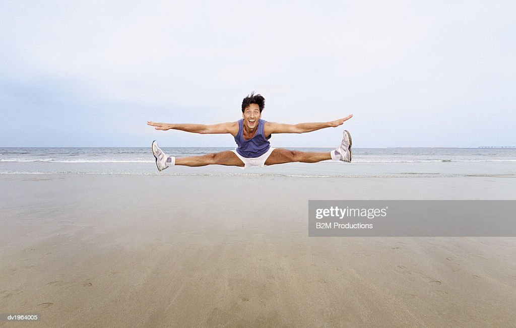 Man in Shorts and Vest Jumps Mid-Air on the Beach, Doing the Splits and Cheering : Stock Photo