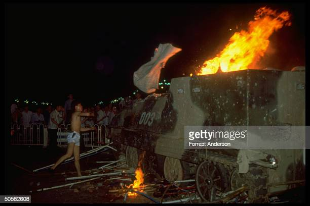Man in shorts hurling white cloth at burning tank while men in bkgrd watch during student prodemocracy protests in Tiananmen Sq