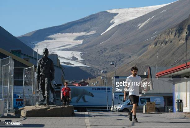 A man in shorts walks in the town center as a melting glacier lies behind during a summer heat wave on Svalbard archipelago on July 30 2020 in...