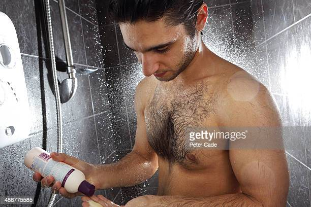 Man in shower putting shampoo into hand