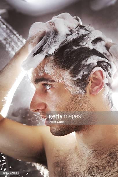 man in shower washing hair