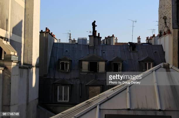 man in silhouette stands on top of chimney in paris - schornsteinfeger stock-fotos und bilder