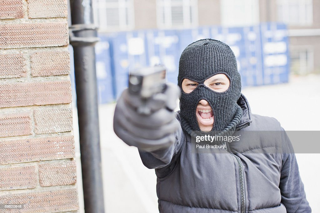 Man in skin mask holding gun : Stock Photo