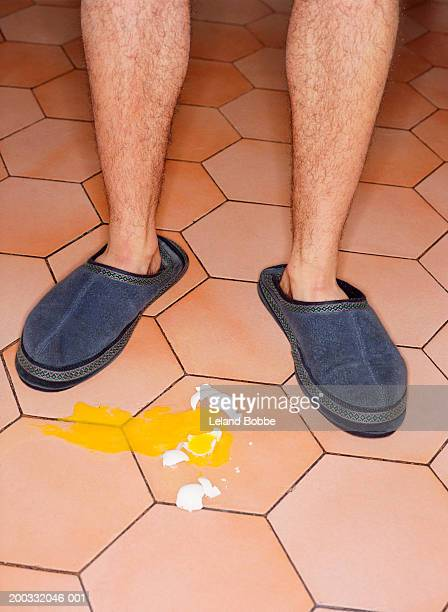 man in slippers standing over broken egg, low section - hairy legs stock photos and pictures