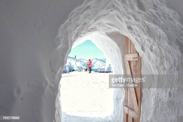 man in snow seen from igloo doorway - igloo stock pictures, royalty-free photos & images