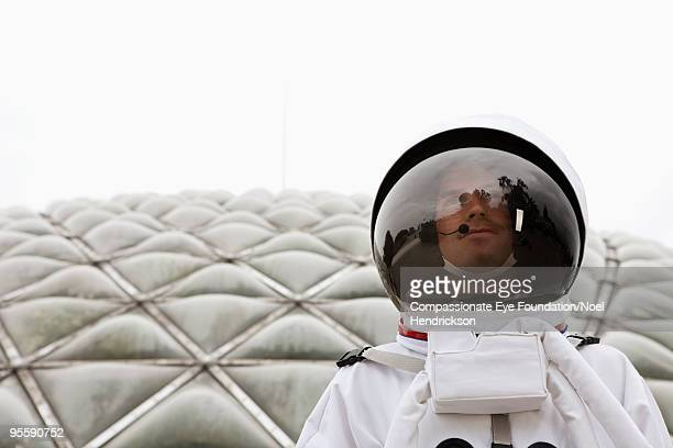 man in space suit in front of biosphere