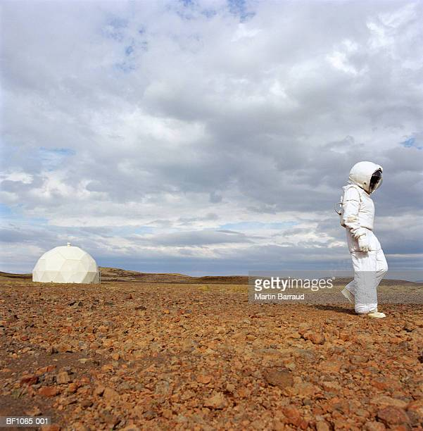 Man in space suit walking across rocky ground, radome in background