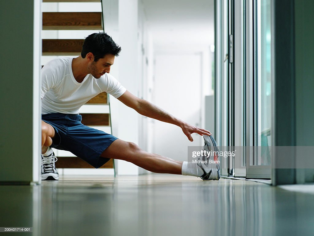 Man in sports clothes performing leg stretch in hallway, ground view : Stock Photo
