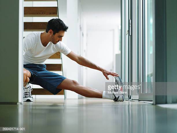man in sports clothes performing leg stretch in hallway, ground view - home workout stock pictures, royalty-free photos & images