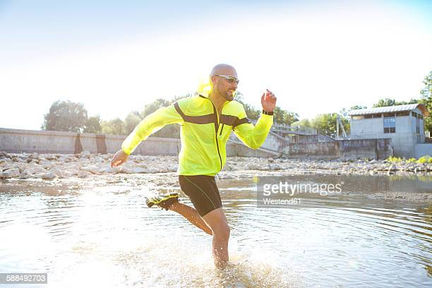 man in sports wear running in water - best sunglasses for bald men stock pictures, royalty-free photos & images
