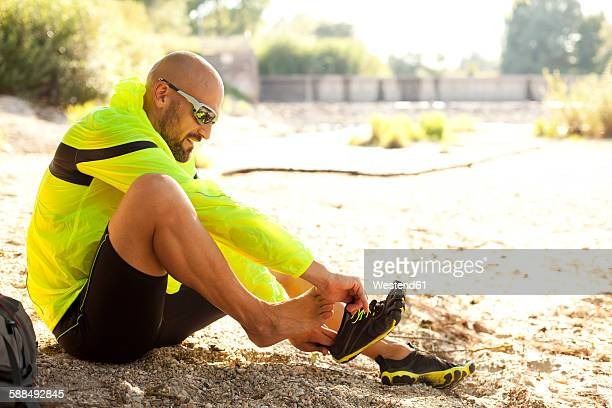 Man in sports wear sitting on ground putting his shoes on