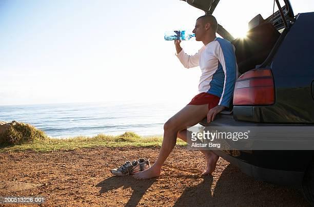Man in sportswear on the open boot of car drinking bottled water