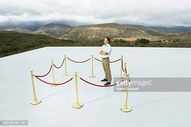 man in square roped off area on platform, arms folded, outdoors - roped off stock pictures, royalty-free photos & images