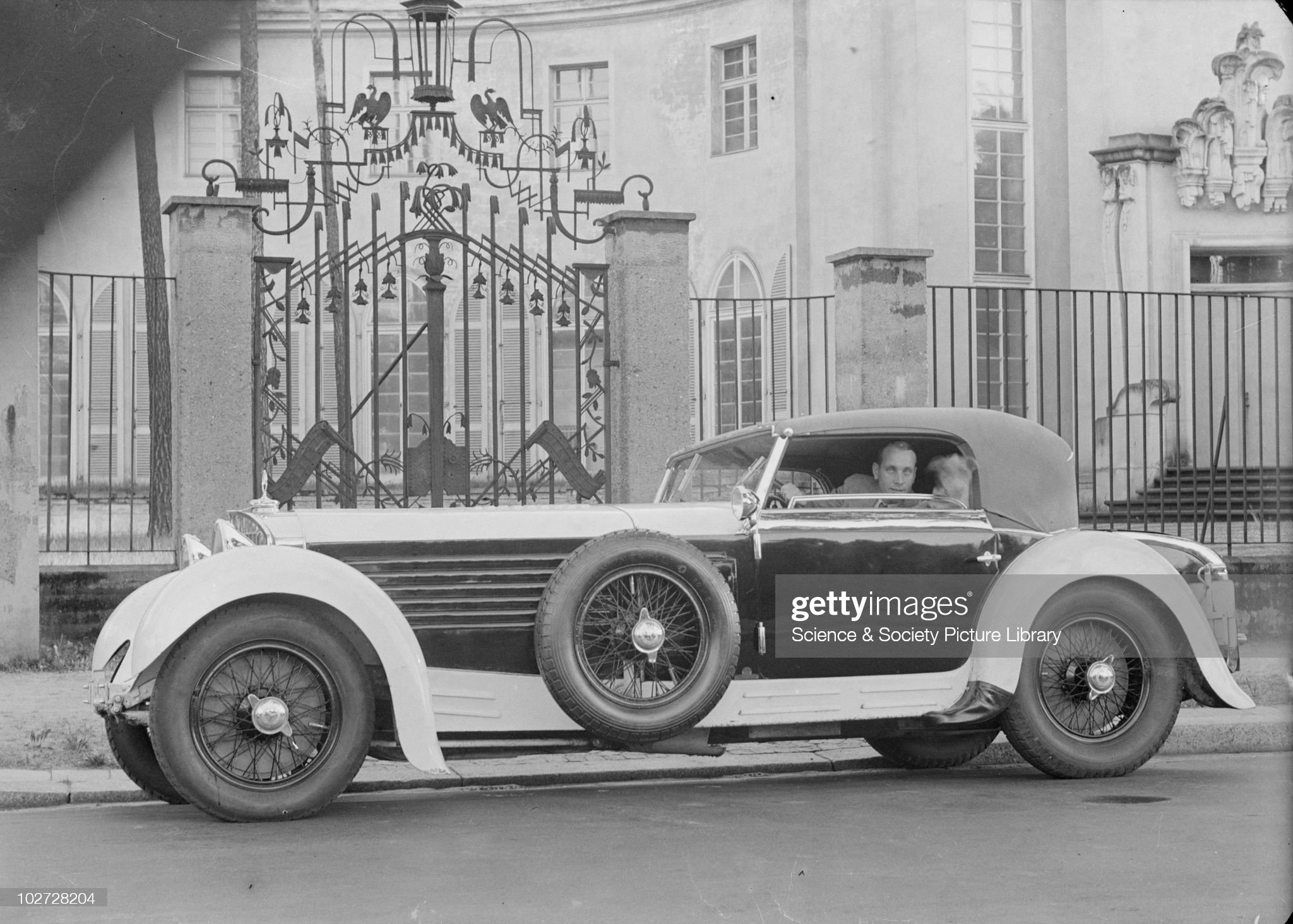 Man in stationary car in front of elaborate gates. Photograph taken by Zoltan Glass, c.1930. : News Photo
