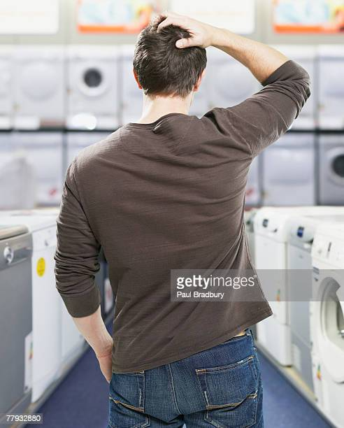 Man in store looking at appliances confused