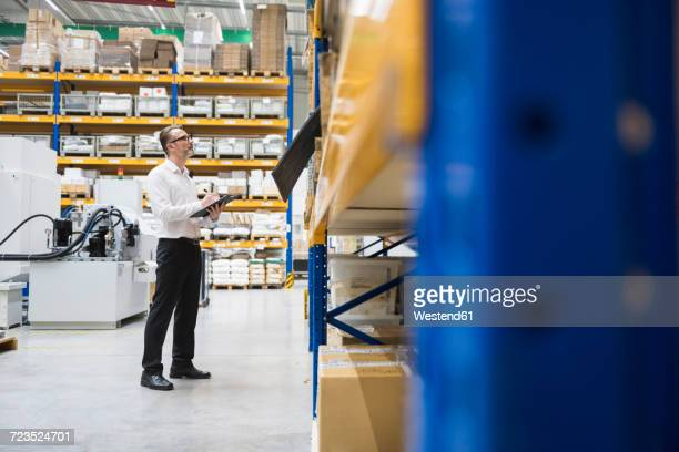 Man in storehouse taking notes