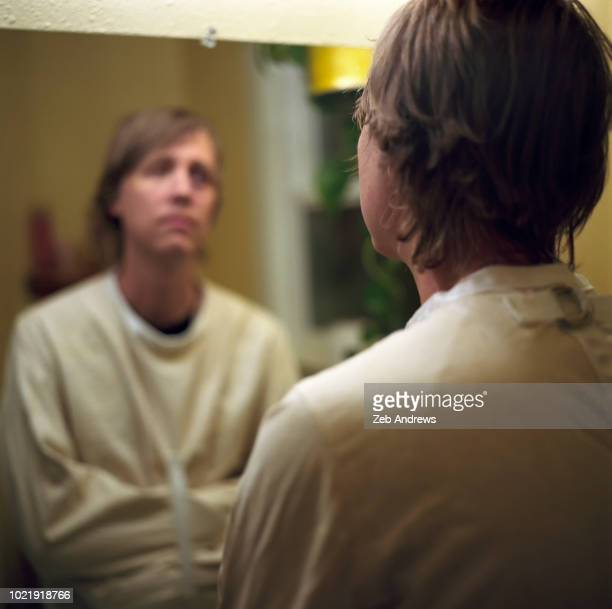 Man in straight jacket staring at himself in bathroom mirror