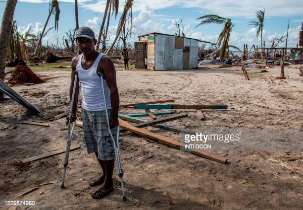 Man in stretchers is pictured as others help him rebuild his house in the devastated Haulover, a community 41 km south of Bilwi, in the Northern...