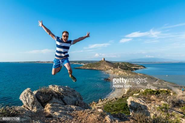 man in striped t-shirt jumping on the rocks at tharros peninsula. tharros, sardinia, italy, europe. - cerdeña fotografías e imágenes de stock